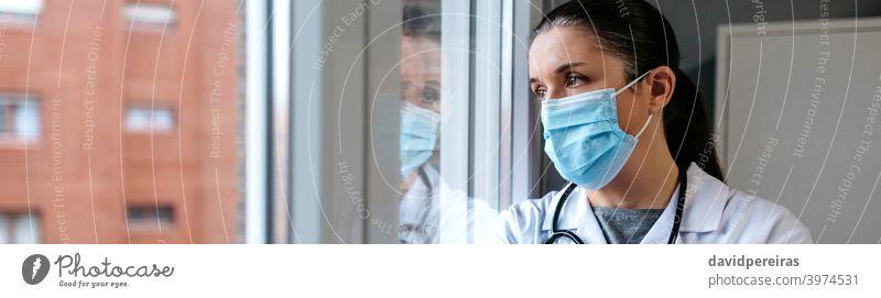 Weiblicher Arzt schaut aus dem Krankenhausfenster Frau Schutzmaske Ausschau haltend Fenster nachdenklich Reflexion & Spiegelung ernst Coronavirus Transparente