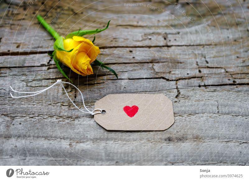 Ein Herz auf einem Etikett und eine gelbe Rose auf einem Holztisch rot Valentinstag Muttertag Liebe Blume Farbfoto Feste & Feiern Stil Nahaufnahme einzeln grau