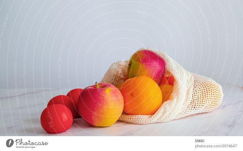 Verschiedene Früchte und Gemüse auf einem weißen Tisch, in einer Stofftasche. Konzept des nachhaltigen Einkaufens und Einkaufens ohne Plastik. Kopierraum