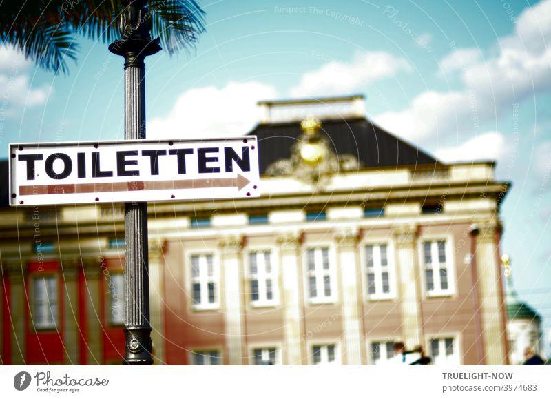 Jetzt aber schnell | wenn's pressiert: Ein gut sichtbares Schild TOILETTEN an historischem Laternenpfahl vor dem wieder aufgebauten Stadtschloss Potsdam,  Residenz der Landesregierung von Brandenburg unter blauem Himmel mit weißen Wolken