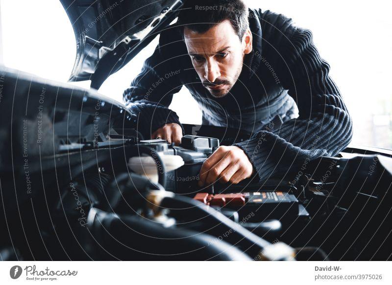 Mann untersucht sein Auto Motorhaube prüfen defekt PKW kontrollieren reparieren kaputt Fahrzeug Kontrolle verärgert sauer