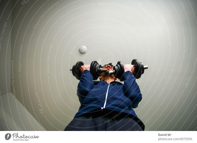 Sportler schnwingt die Hanteln Krafttraining Kurzhantel trainieren disziplin Vorsätze Fitness sportlich stark Mann