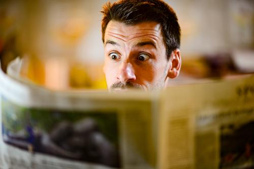 Mann schaut überrascht in die Zeitung lesen News Nachrichten Medien Presse aktuell Informationen Welt Gesichtsausdruck erstaunt schockiert
