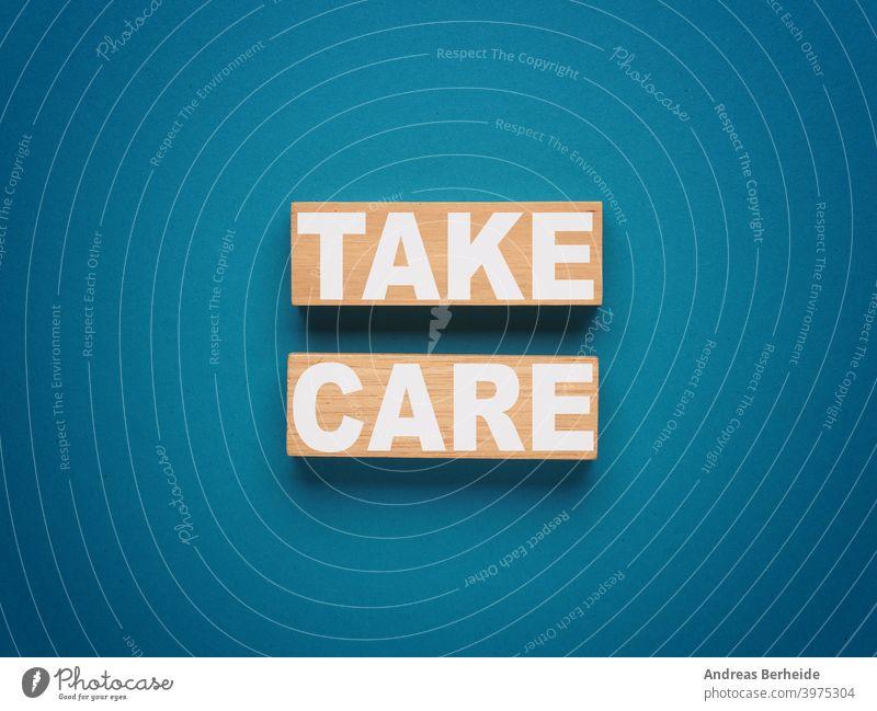 Zwei Holzblöcke mit der Aufschrift TAKE CARE auf blauem Hintergrund Motivation Selbstversorgung gesundes Leben gut Prävention healtcare Erholung Meditation