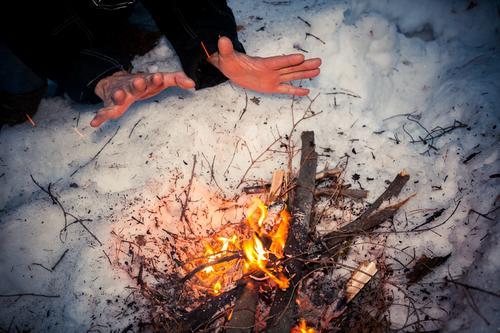 Gefrorene Männerhände wärmen sich in der Winternacht am Lagerfeuer. Hände Brennholz Erwärmung weiß Schnee Nacht Hintergrund Brand Freudenfeuer hell Brandwunde
