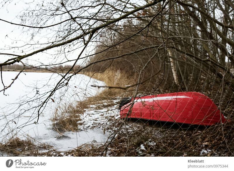 Am Ufer liegendes, halb verstecktes  rotes Boot wartet auf den Frühling - der See ist zugefroren Rotes Boot, See, Wasserfahrzeug zugefrorener see paddelboot