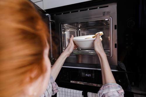Frau erwärmt Essen in der Mikrowelle. In Möbel eingebaute Küchengeräte. Lebensmittel Ofen Heizung Kulisse Zeitschaltuhr Essen zubereiten Koch heimwärts