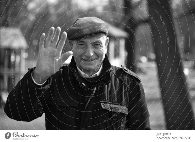 Senior winkt freundlich in die Kamera Mann winken Freundlichkeit nett Männlicher Senior Mensch maskulin Großvater Leben Blick Erwachsene Blick in die Kamera