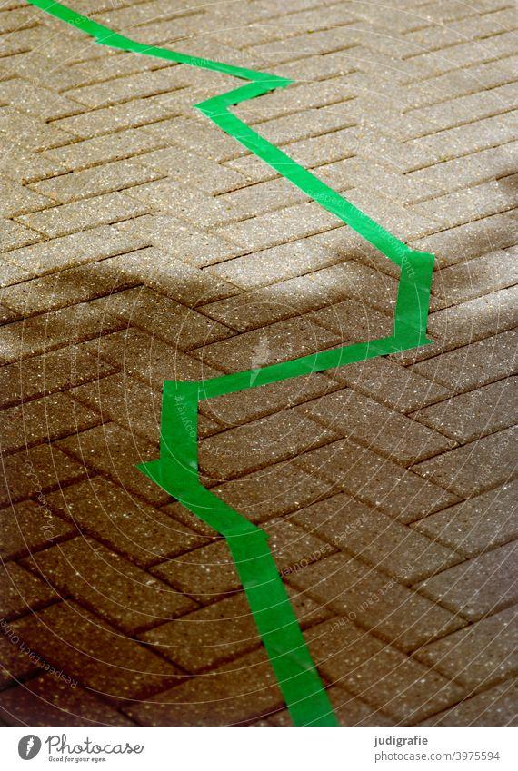 Zickzack in grün auf Straßenpflaster Linie Markierung Markierungslinie Wege & Pfade Pflastersteine gepflastert Schatten Licht Stadt Stein Grenze Muster