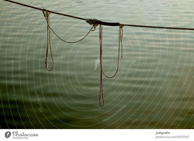 Hafen. Verknotete Seile hängen über der Wasseroberfläche. Tau Strick Knoten Stilleben Ruhe maritim Befestigung Schifffahrt