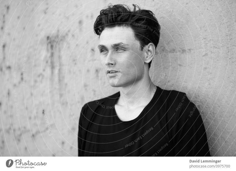 Junge Handsome Male Model vor einer Wand Schwarz und Weiß Porträt männlich Mann Teenager jung Junger Mann Jugendliche junger Erwachsener krause Haare