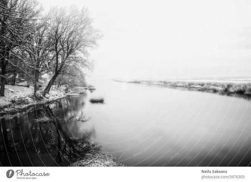 ruhiges Wasser im lettischen Winter / Fluss in der Nähe meines Hauses / der Tag, an dem sich Eis auf dem Wasser bildet / Sonnenaufgang über dem Land Herbst