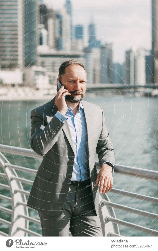 Junger Geschäftsmann mit einem Telefon in den Händen, stehend in einer großen Stadt zwischen Hochhäusern Büro Mann Smartphone modern gelungen Großstadt Anzug
