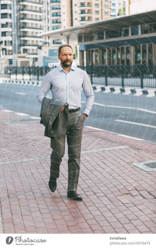 Porträt eines jungen Millennials, der mit einem Telefon in der Hand durch die Stadt läuft Büro Mann Geschäftsmann Smartphone modern gelungen Großstadt Anzug