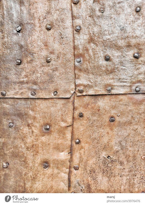 Zeitgeschichte | 4 genietete, rostige Blechtafeln, die eine Tür oder Fassade vor Einbrechern und Witterung schützen Patchwork Handwerk flicken Kontrast