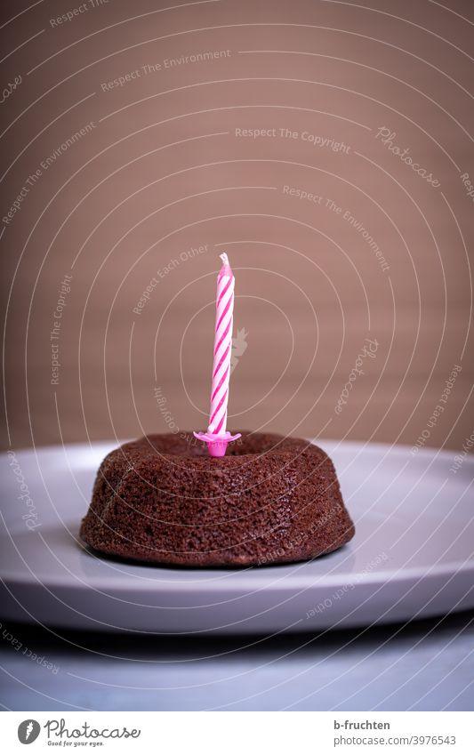 Kleiner Schokoladekuchen mit einer Geburtstagskerze Kuchen einzeln Feste & Feiern Geburtstagstorte lecker Innenaufnahme süß Backwaren Kerze Teller pink