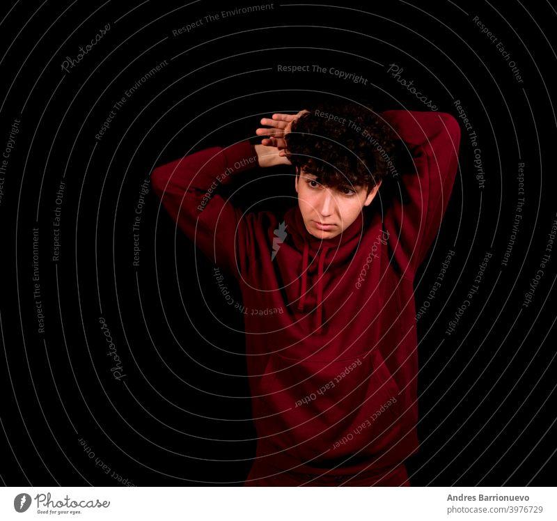 Attraktiver junger Mann mit lockigem Haar posiert auf schwarzem Studio Hintergrund Kosmetik Frisur Vorschein Atelier schließen Freizeitkleidung photogen weiß