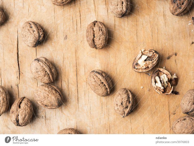 Walnuss in der Schale auf einem Holztisch Walnussholz ganz hölzern Hintergrund gebrochen braun Nahaufnahme geknackt Lebensmittel frisch Frucht Menschengruppe