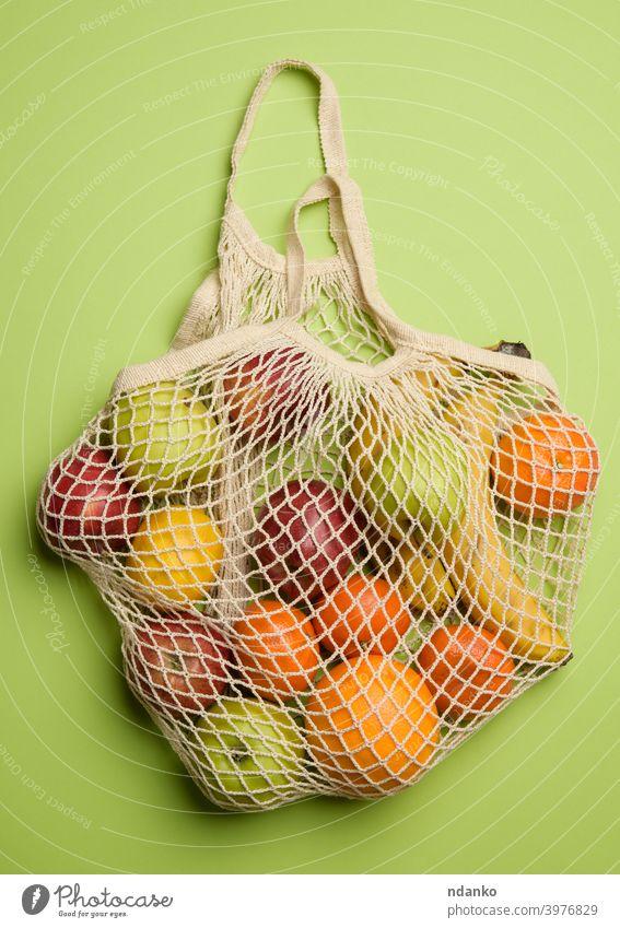 reifen frischen Früchten in einem Textil String Tasche auf einem grünen Hintergrund orange Apfel Banane Konzept Baumwolle Öko ökologisch Ökologie Lebensmittel