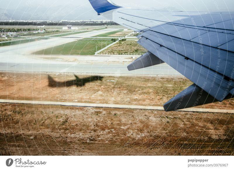 Ab in den Urlaub, Schatten eines Flugzeugs beim Start Flugzeugausblick Flugzeugstart starten Luftverkehr Farbfoto Außenaufnahme Passagierflugzeug