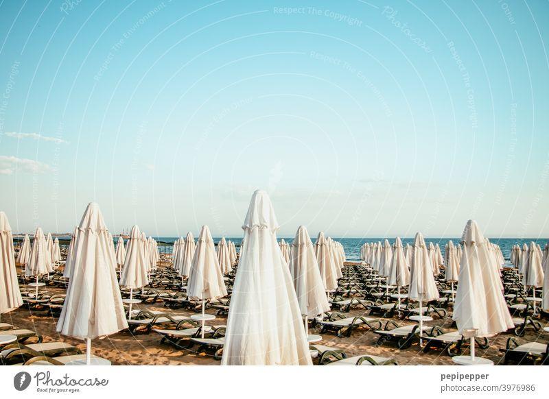 geschlossene Sonnenschirme mit leeren Strandliegen in Corona-Zeiten Sommer Himmel blau Ferien & Urlaub & Reisen Meer Erholung Sand Küste Tourismus Sommerurlaub
