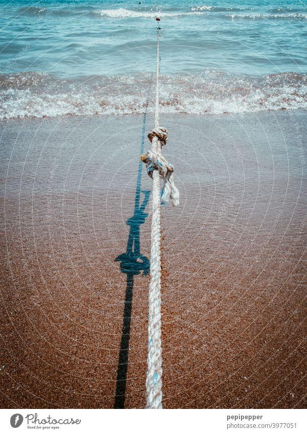 ein gespanntes Seil am Strand das ein Boot festhält maritim Wasserfahrzeug Tau Außenaufnahme Befestigung Küste Nahaufnahme Knoten Knotenpunkt festhalten