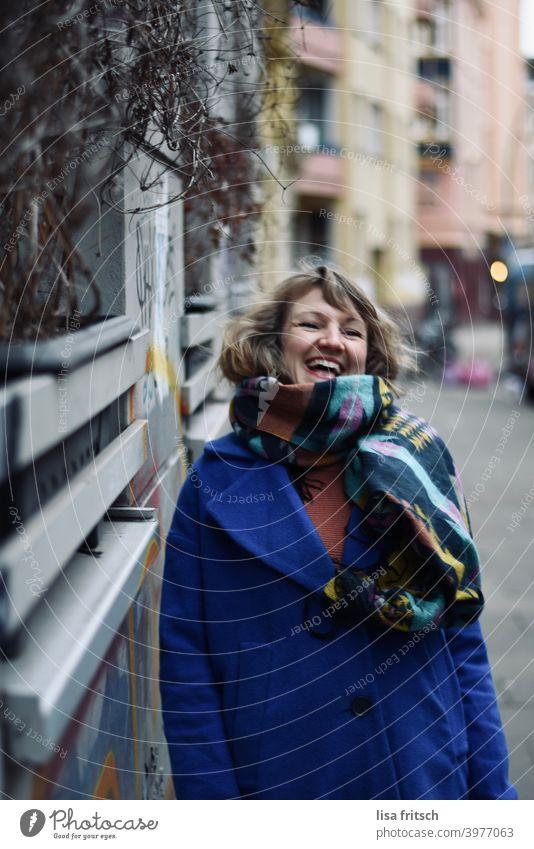 LACHEN - GLÜCKLICH - LEBEN Frau blond Locken Winter Herbst Schal Jacke blau Hauswand Freude Lebensfreude Außenaufnahme Farbfoto Fröhlichkeit schön feminin
