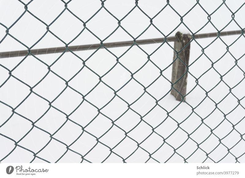 Am Rande eines Sportplatzen im Winter mit Maschendrahtzaun und Abgrenzung für Zuschauer Schnee Maschendrahtzaum menschenleer Schneefläche weiß schwarz sauber