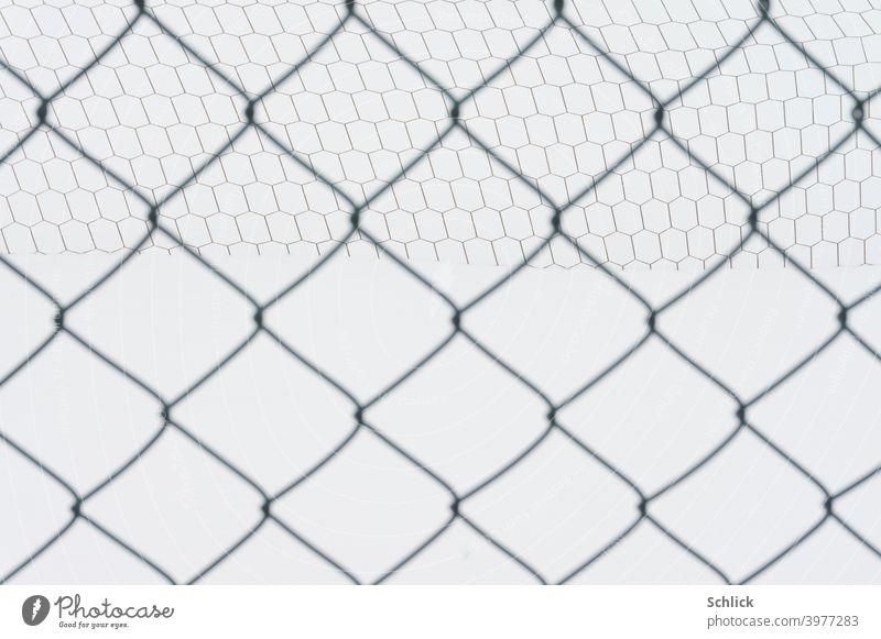 Leerer Fußballplatz im Schnee mit Tornetz un Maschendrahtzaun Netz Zaun Winter verschneit Schneefläche Rauten Quadrate Sechsecke Polygone abstrakt außen