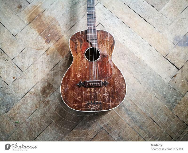 Alte braune defekte Gitarre mit gerissener Saite auf dem schönen alten Holzboden eines Bauernhaus in Oberbayern Musikinstrument Hippie kaputt Musiker Patina