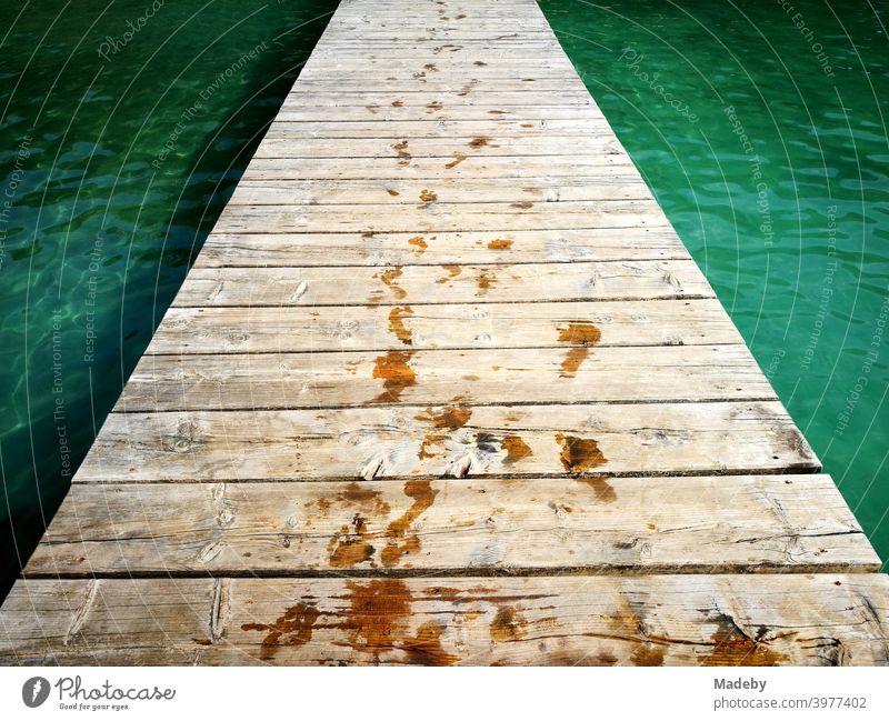 Bootssteg oder Badesteg aus schönem alten Holz im Sommer bei Sonnenschein am Alpsee in Schwangau bei Füssen im Allgäu im Freistaat Bayern Steg Holzsteg See