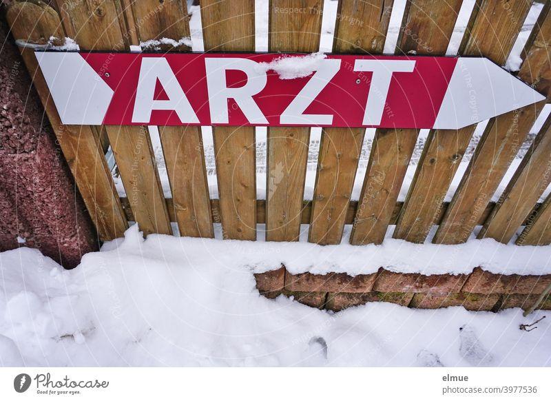 """Schild als großer Pfeil und mit der Aufschrift """"ARZT"""" in Druckbuchstaben ist an einem Holzlattenzaun befestigt / ärztliche Hilfe / Orientierung Arzt Hinweis"""