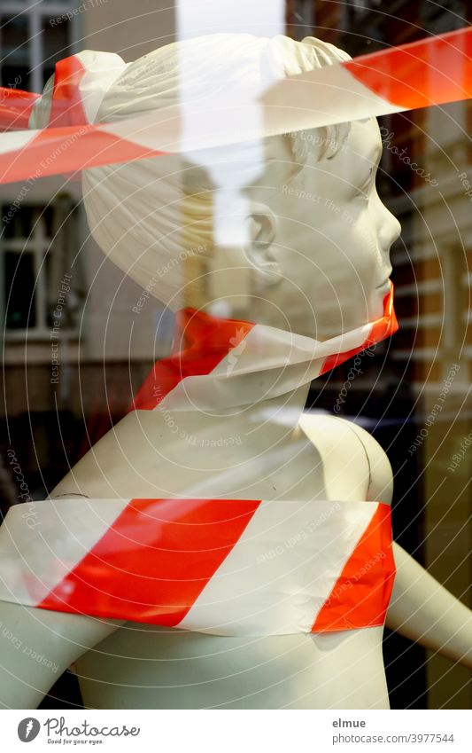 Im Schaufenster steht eine weiße, kindliche Schaufensterpuppe mit rot-weißem Absperrband umwickelt / Geschäftsauflösung / Ausverkauf / Sale Flatterband
