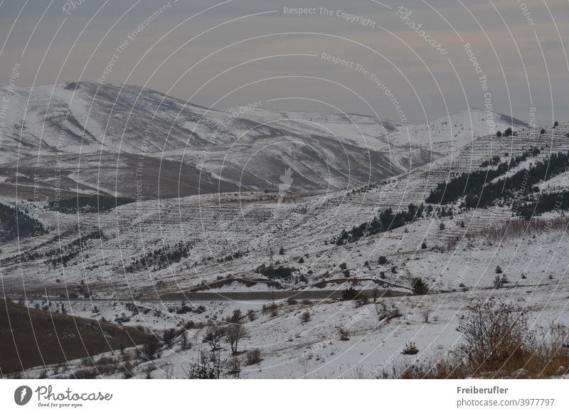 Bergige Landschaft mit frisch Schnee bedeckt Steppen hafte Botanik teilweise bewaldet weite Sicht ins Land auf dem eine Straße führt ruhig Menschenleer