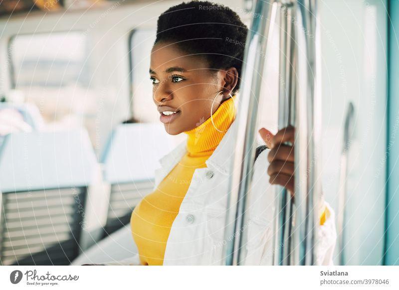 Porträt einer jungen afrikanischen Frau, die mit der U-Bahn fährt Afrikanisch Stehen Zug Lächeln im Inneren Passagier urban schwarze Frauen schwarze Millennials