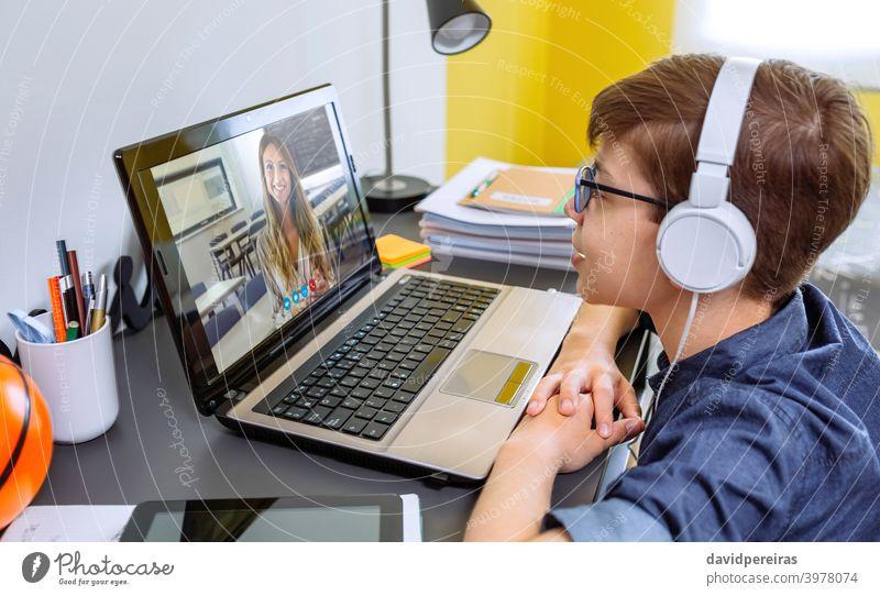 Junge mit Kopfhörer erhalten Klasse zu Hause mit Laptop aus seinem Schlafzimmer Heimunterricht Schule zu Hause Lehrer Videoanruf Jugendzimmer sprechend