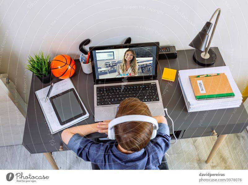 Draufsicht auf einen nicht erkennbaren Jungen mit Kopfhörern, der zu Hause mit einem Laptop Unterricht erhält unkenntlich Teenager Lehrer Schule zu Hause