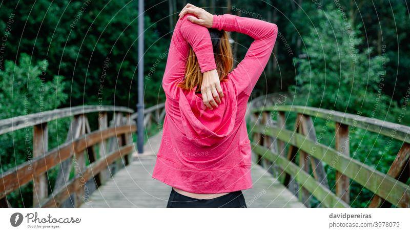 Nicht erkennbare Sportlerin, die im Freien die Arme streckt. unkenntlich Athlet Frau strecken Waffen rückwärts Taille hoch Gesundheit Netz Transparente