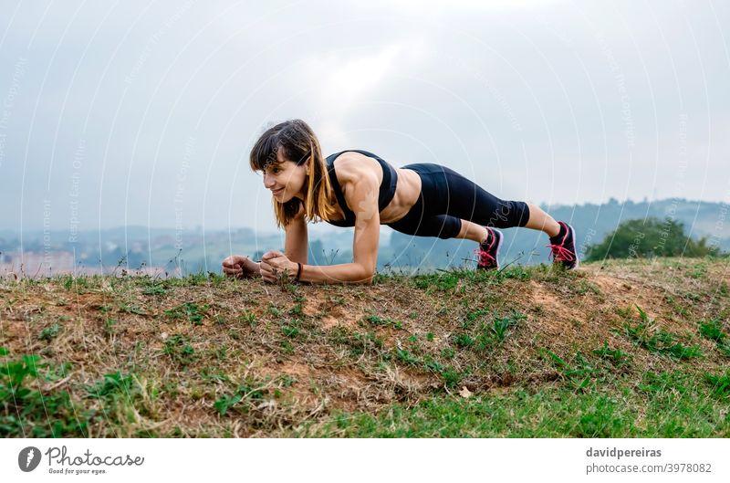 Weibliche Athletin trainiert auf dem Brett Frau Schiffsplanken Lächeln Morgen Training Bauchmuskeln genießend Ausdauer anstrengen im Freien Sportlerin Fitness