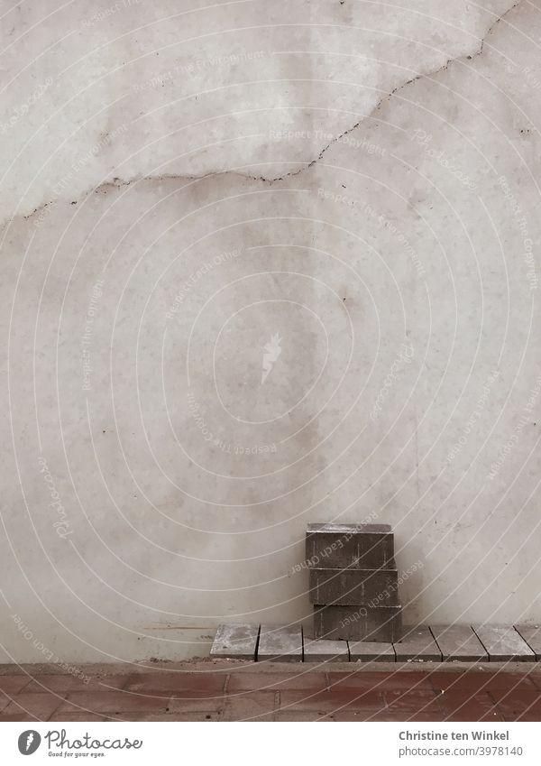 Kleine Baustelle... Letzte Pflasterarbeiten vor einer Betonmauer... Drei gestapelte Pflastersteine warten auf ihren Einsatz pflastern Steine Mauer Gehweg