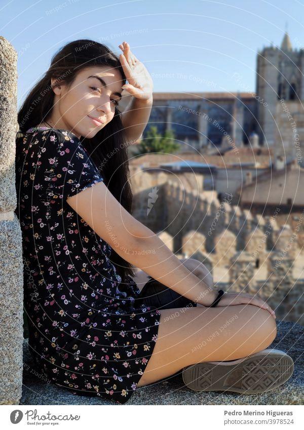 Schöne Frau, die die Sonne mit ihrer Hand verdeckt, sitzt auf einer Mauer Frauen Schönheit weißes Mädchen Kaukasier braune Haare Model Kleid Wand Kathedrale