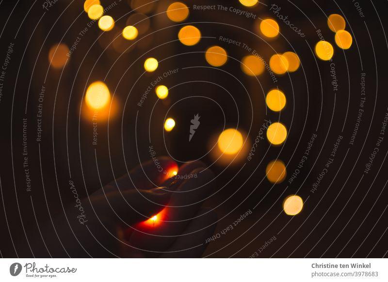 Spielerei mit Lichterkette und Kerzenlicht. Hand hält eine Lichterkette. Defokussierte Lichtpunkte vor dunklem Hintergrund. glänzen Dämmerung Unschärfe Abend