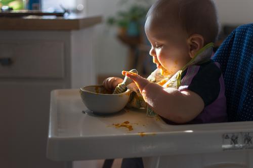 Baby sitzt im Hochstuhl und greift nach dem Löffel; dramatische natürliche Beleuchtung und unordentlicher Tabletttisch babygeführte Entwöhnung