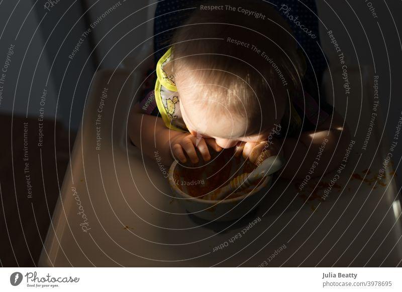 Baby kaut auf Silikonschale, während es im Hochstuhl sitzt; dramatische natürliche Beleuchtung babygeführte Entwöhnung erste Lebensmittel Fingerfood