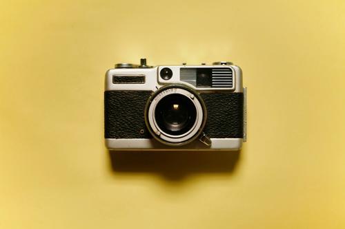 Vorderansicht einer analogen Vintage-Fotokamera isoliert auf gelbem Hintergrund alt Gerät Filmmaterial Linse Antiquität klassisch Fotografie retro altehrwürdig
