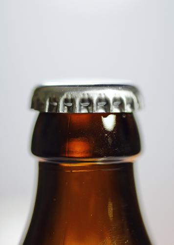 Kronenkorken auf einer geschlossenen Bierflasche Kronkorken Flasche Verschluss Metall Glas Getränk verschlossen braun silber
