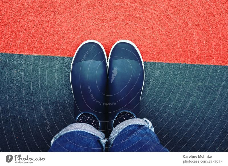 Frau steht in blauen Halbgummistiefeln und Jeans auf rotblauem Boden Schuhe Regenboots Gummistiefel Stiefel Außenaufnahme nass Wasser Farbfoto Wetter