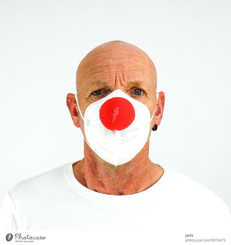 Mann mit FFP2 Maske und roter Clownsnase Mundschutz ffp2-maske Mund-Nasen-Maske clownsnase Fasching Karneval Augen Falten Schutz covid-19 Pandemie Optimismus