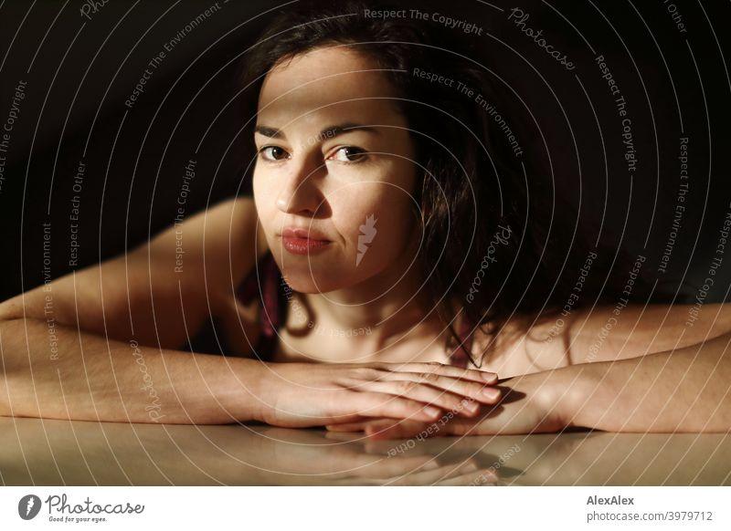 Porträt einer jungen Frau, die mit dem Arm auf dem Tisch liegt, Spiel von Licht und Schatten natürlich hübsch brünett langhaarig lange Haare schlank passen