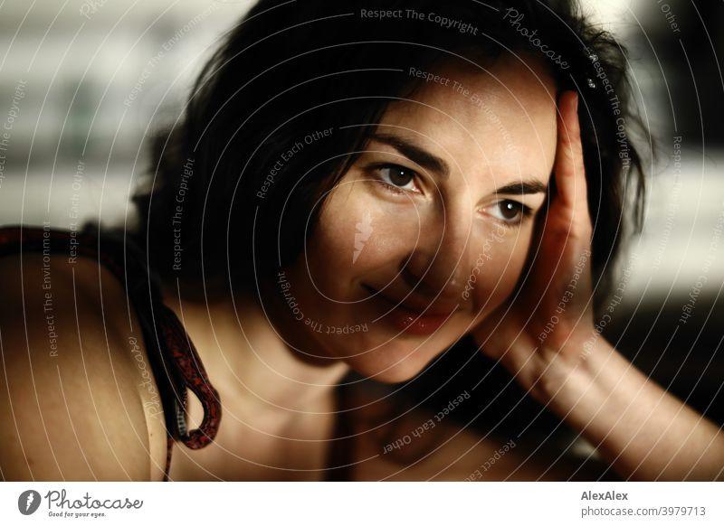 Porträt einer jungen, brünetten, langhaarigen Frau mit Licht- und Schattenspiel natürlich hübsch lange Haare schlank passen Schulter Haut Fragen seitlich gerade